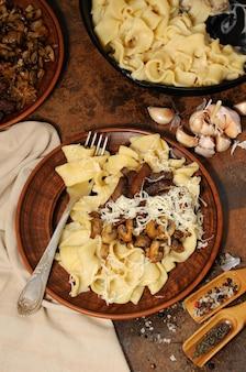 揚げシャンピニオン、ビーフストロガノフ、チーズで味付けしたタマネギのパスタフェットチーネ