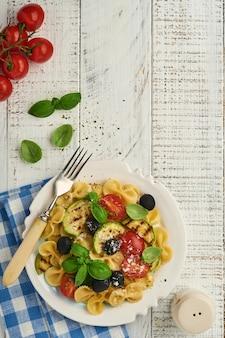 Салат из пасты фиокки с овощами на гриле цукини, помидорами черри, оливками, базиликом и сыром пармезан в белой тарелке на светлом сланцевом, каменном или бетонном фоне. концепция обеда. вид сверху