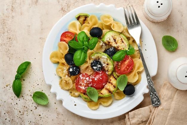 야채와 함께 파스타 fiocchi 샐러드는 가벼운 슬레이트, 돌 또는 콘크리트 배경에 흰색 접시에 호박, 체리 토마토, 올리브, 바질, 파르 메산 치즈를 구 웠습니다. 점심 개념. 평면도.