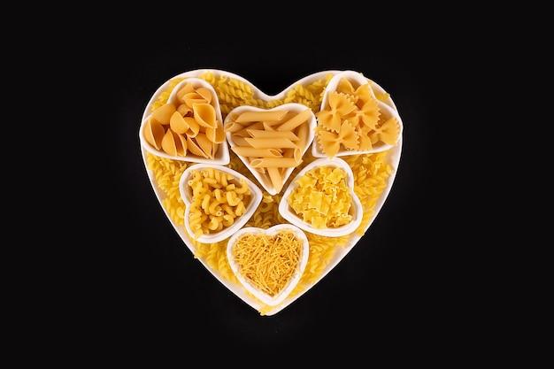검정 배경 위에 심장 모양의 도자기 접시에 파스타 음식 선택
