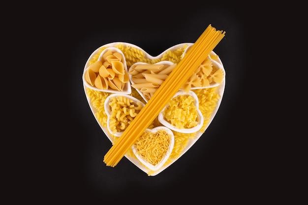 검은 표면 위에 심장 모양의 도자기 접시에 파스타 음식 선택