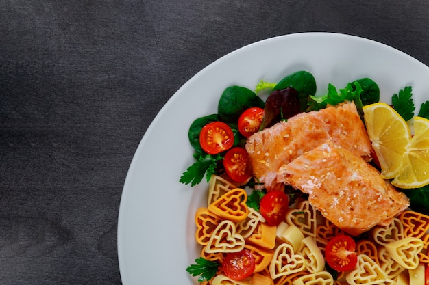 Pasta in the form of a heart salad with salmon and vegetables