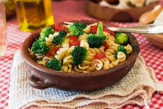 Pasta fusilli with tomato and broccoli in the earthenware
