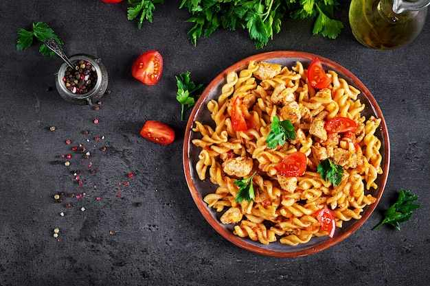 Pasta fusilli with tomatoes, chicken meat and parsley on plate on dark table