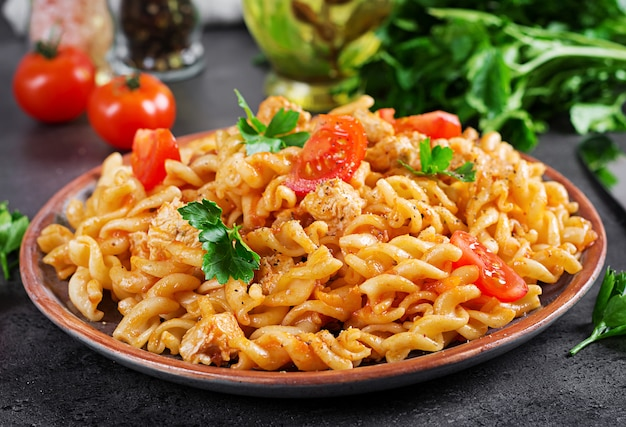 Pasta fusilli  with tomatoes, chicken meat and parsley on plate on dark table.