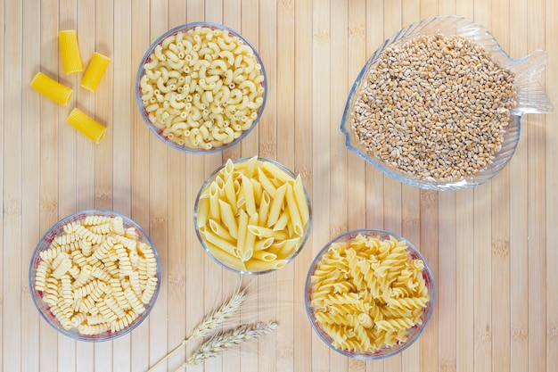Pasta in glass plates. wheat grains. wheat spikelets. flat lay