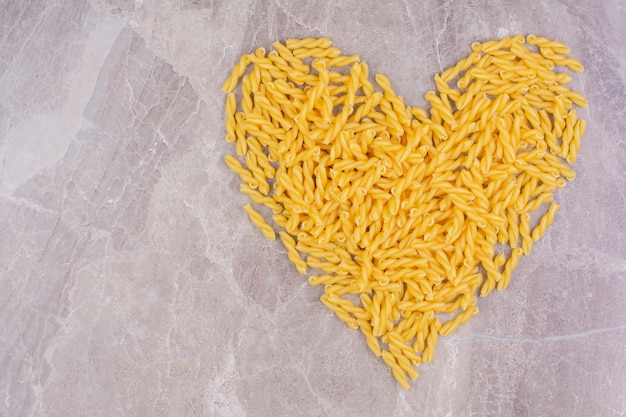 Pasta in a heart shape on the marble space.