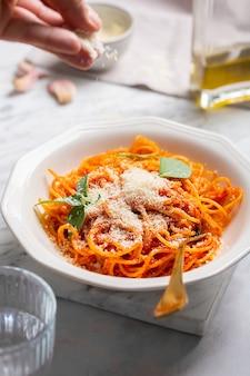 Паста в тарелке в томатном соусе, посыпанная пармезаном руками
