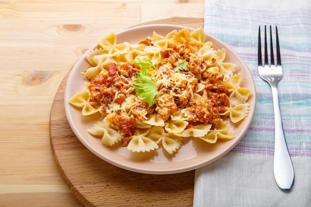 Паста в томатном соусе болоньезе в тарелке на деревянном столе на салфетке рядом с вилкой горизонтальное фото