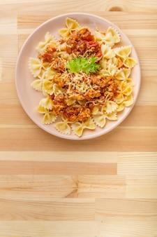 木製のテーブルの上のプレートにトマトボロネーゼソースのパスタ