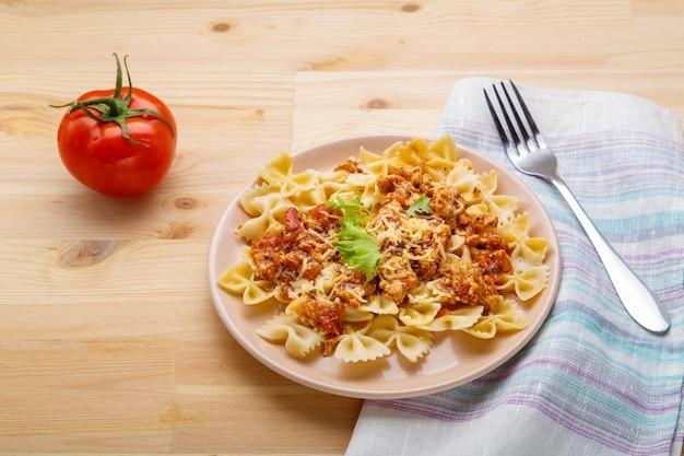 フォークとトマトの横にあるナプキンのテーブルの上のプレートにトマトボロネーゼソースのパスタ