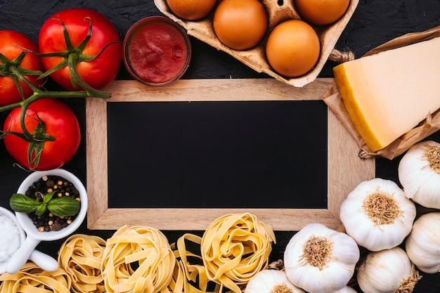 Pasta ingredients around blckboard