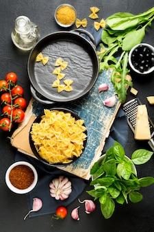 Паста ингредиенты. помидоры черри, паста фарфалле, чеснок, базилик, пармезан, шпинат, руккола, специи и оливковое масло на темном фоне