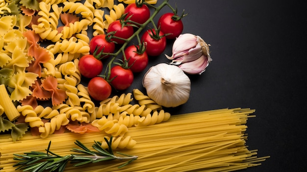 Pasta and ingredients for cooking on dark backdrop