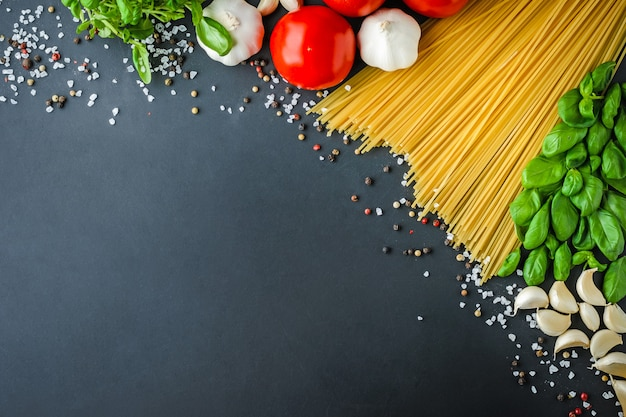 Pasta and ingredients for cooking on dark background, top view