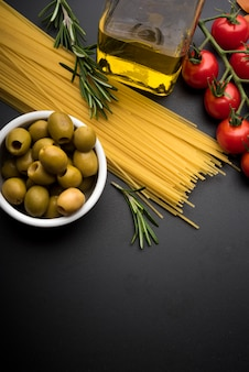Pasta and ingredients for cooking on dark background