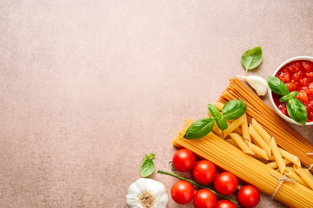 Pasta ingredients on light rustic background with copyspace