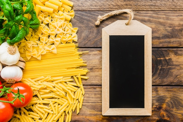 Pasta ingredients near blank chalkboard