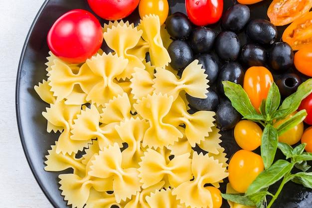 パスタの材料、生パスタ、チェリートマト、オリーブ、バジルの葉のクローズアップ