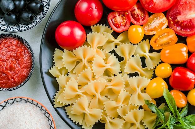 파스타 재료, 생 파스타, 체리 토마토, 올리브 및 바질 잎은 검정 접시에
