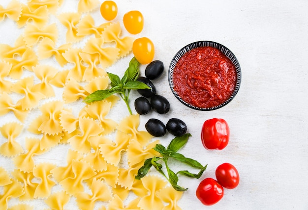 Pasta ingredients, raw pasta, cherry tomatoes, olives and basil leaves on the white background