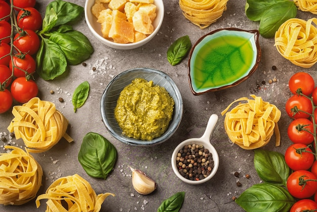 Pasta, ingredients and spices on a table with a dish, pesto sauce.