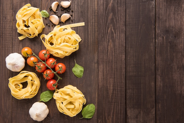 パスタの材料。トマト、ニンニク、コショウ、および木製の背景にキノコ