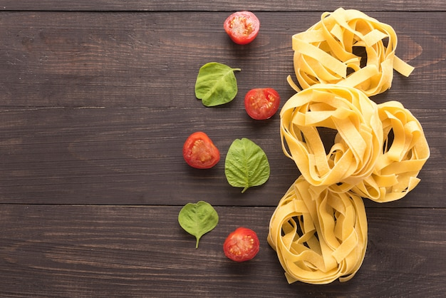 Pasta ingredients. tomato on the wooden background