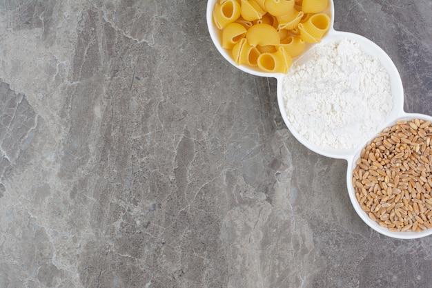 Pasta e ingredienti in coppe di ceramica bianca.