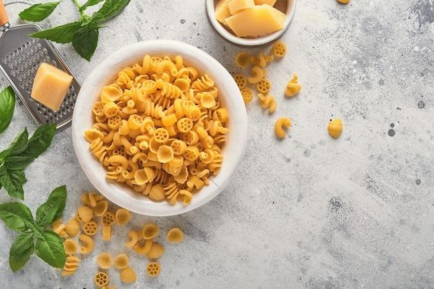 파스타. 이탈리아 파스타. 인살라타 디 파스타와 야채 요리 재료, 치즈, 바질은 오래된 석조 배경에 있습니다. 이탈리아 음식 요리 재료. 복사 공간이 있는 상위 뷰입니다.