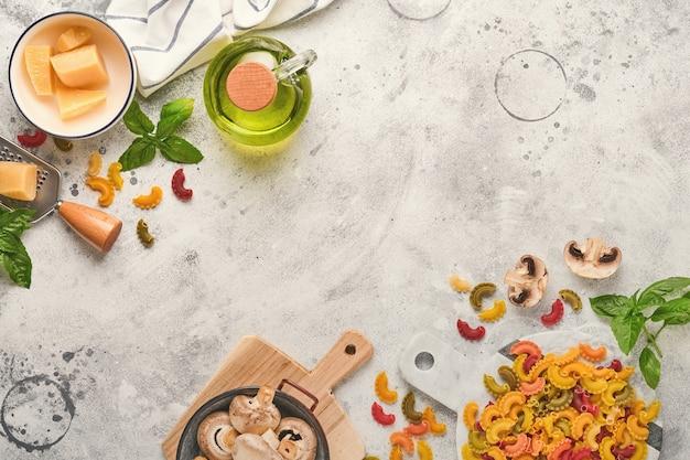 파스타. 이탈리아 파스타. 인살라타 디 파스타와 야채 요리 재료, 치즈, 버섯, 바질은 오래된 석조 배경에 있습니다. 이탈리아 음식 요리 재료. 복사 공간이 있는 상위 뷰입니다.