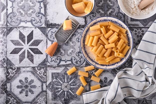 파스타. 이탈리아 파스타. 리가토니와 야채는 오래된 돌 배경에서 재료를 요리합니다. 이탈리아 음식 요리 재료. 복사 공간이 있는 상위 뷰입니다.