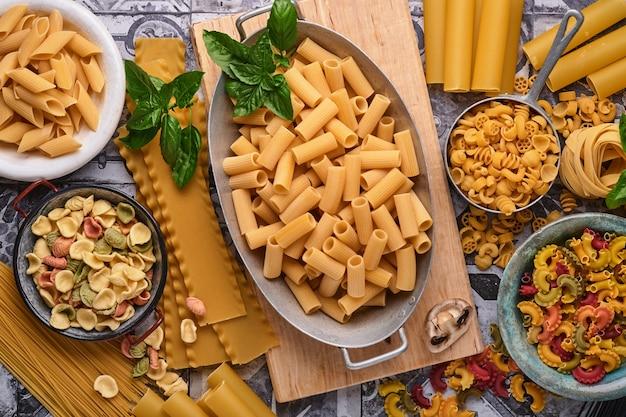 파스타. 이탈리아 파스타. 다양한 전통 이탈리아 파스타:다채로운 스파게티, 탈리아텔레, 파르팔레, 펜네, 프티티트, 국수, 푸실리, 카넬로니가 오래된 석조 배경에 있습니다. 복사 공간이 있는 상위 뷰입니다.