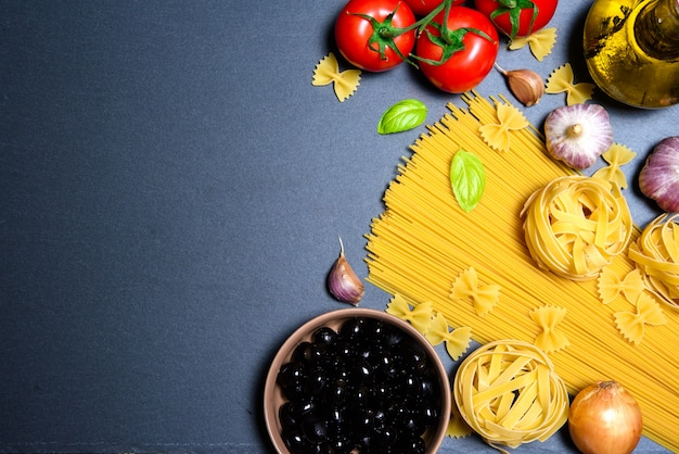 Pasta or italian spaghetti with ingredients on black stone slate background. copyspace