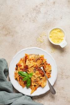 소박한 콘크리트 조명 테이블 배경에 클래식 토마토 소스, 치즈와 바질 파스타 maltagliati. 전통적인 이탈리아 요리 제공. 평면도.