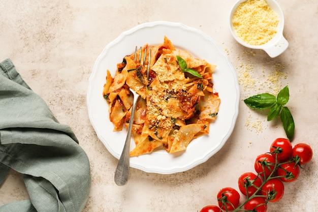 Паста мальтаглиати с классическим томатным соусом, пармезаном и базиликом на деревенском бетонном светлом столе. подача традиционных итальянских блюд. вид сверху.