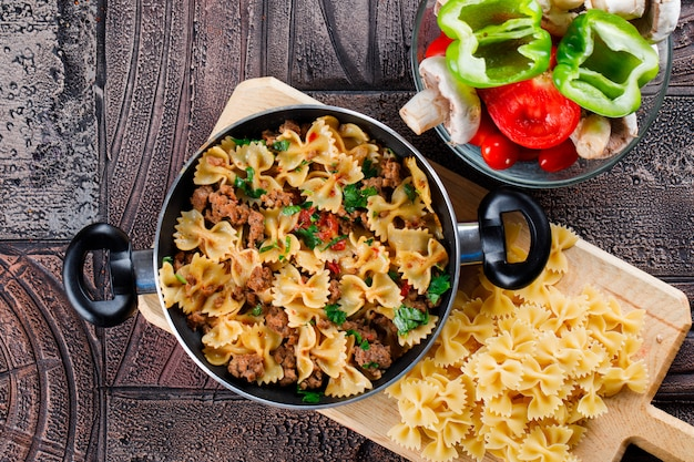Pasta meal in pan with mushroom, pepper, tomato, raw pasta