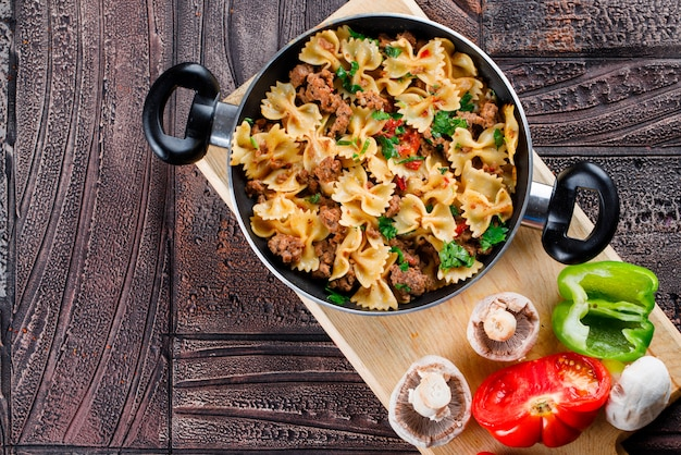 Pasta meal in pan with mushrooms, pepper, tomato