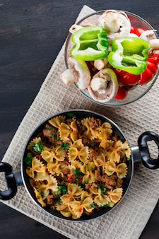 Pasto di pasta in padella con funghi, peperoni, pomodori