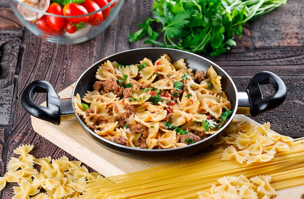Pasta meal in pan with raw pasta, mushroom, parsley, tomato
