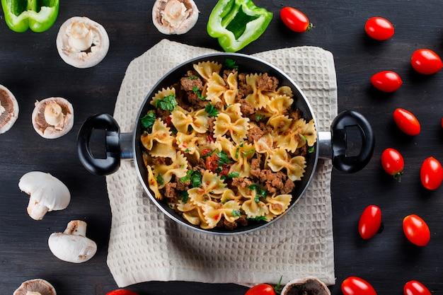 Pasto di pasta con funghi, peperoni, pomodori in padella