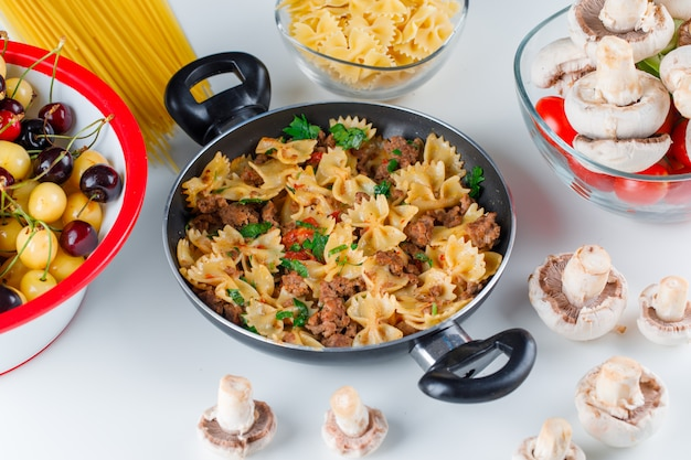Pasta meal with raw pasta, mushroom, tomato, cherry in a pan