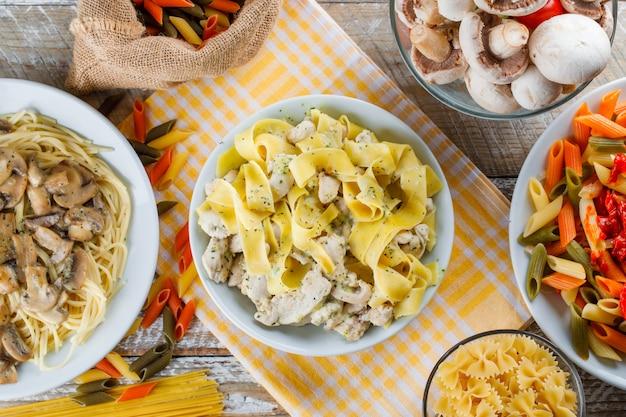 Макаронные блюда в тарелках с сырой пастой, грибами
