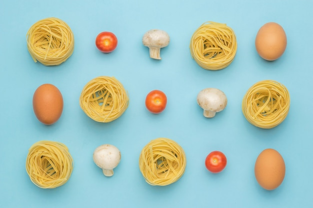 Pasta, mushrooms, eggs and tomatoes on a blue surface. ingredients for making pasta.