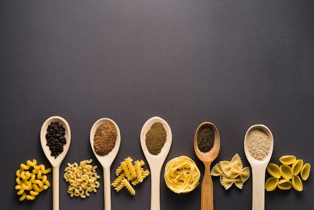 Pasta vicino a cucchiai con spezie