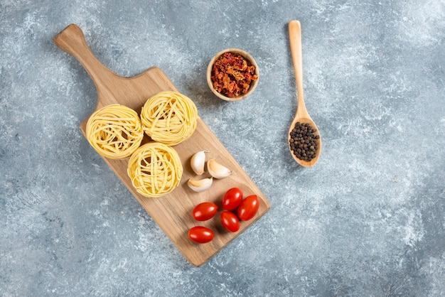 Pasta nests, garlic and cherry tomatoes on wooden board.