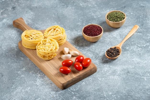 Nidi di pasta, aglio e pomodorini su tavola di legno.