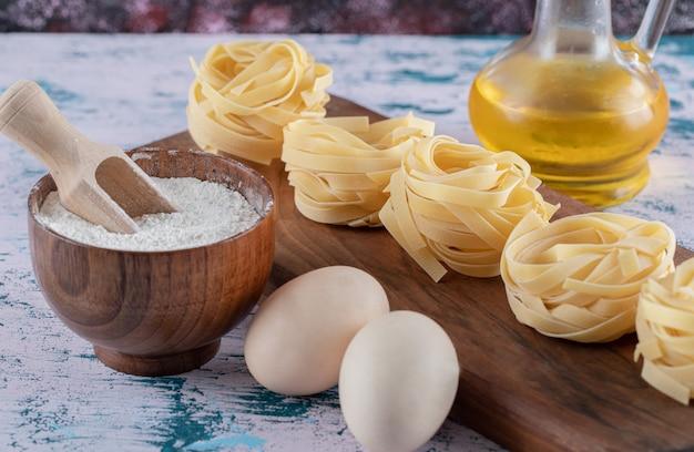 Nidi di pasta su tavola di legno con farina, uova e olio d'oliva.