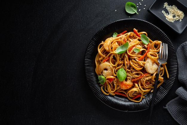 Pasta noodles spaghetti asian with shrimps vegetables and sesame.