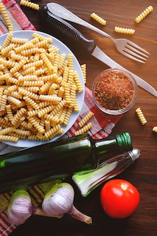 Pasta, olive oil, spices, tomatoes, salt, garlic, knife and fork lie on a dark wooden table. top view